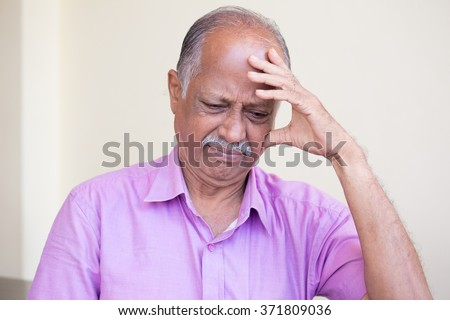 Closeup portrait, morose elderly pensioner, downcast gloomy, resting hand on head, isolated indoors home background - stock photo