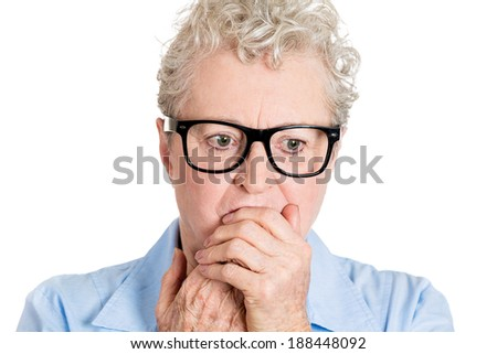 Closeup portrait, nerd, senior mature woman with black glasses,  biting hands nervously, looking down, isolated white background. Mental health, emotion facial expression feeling - stock photo