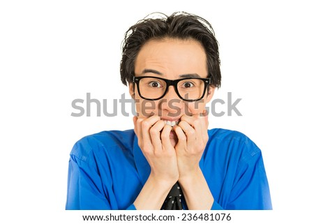 Closeup portrait nerdy young guy with black glasses biting his nails craving something looking anxious isolated white background. Human face expression emotion feeling perception body language