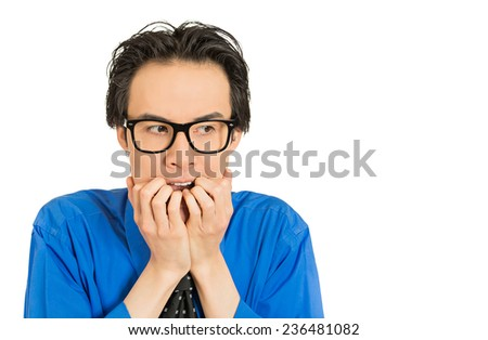 Closeup portrait nerdy young guy with black glasses biting his nails craving something looking anxious isolated white background. Human face expression emotion feeling perception body language - stock photo