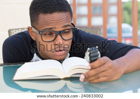 Closeup portrait, nerdy young man in big black glasses holding watch, falling very tired of reading, isolated outdoors outside background. The clock is ticking, can't focus - stock photo