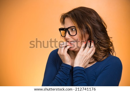 Closeup portrait nervous woman with glasses biting her fingernails craving something, anxious isolated orange background copy space. Negative human emotion facial expression body language perception - stock photo