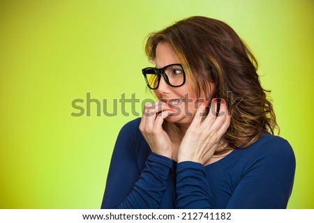 Closeup portrait nervous woman with glasses biting her fingernails craving something, anxious isolated green background copy space. Negative human emotion facial expression body language perception - stock photo