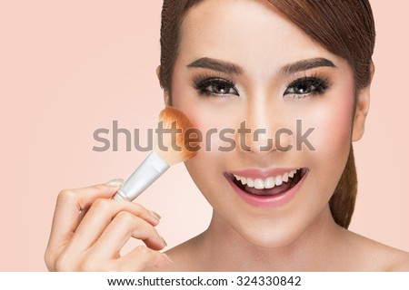 Closeup portrait of a asian woman applying dry cosmetic tonal foundation on the face using makeup brush, on pink background with clipping path. - stock photo
