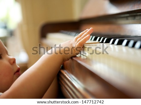 closeup portrait of a baby playing the piano - stock photo