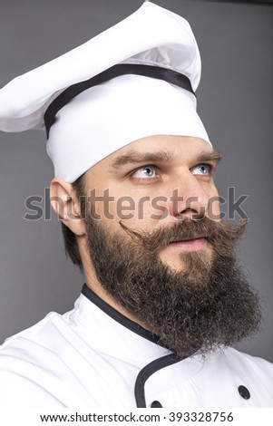 Closeup portrait of a bearded chef over gray background - stock photo
