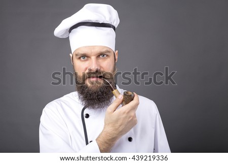 Closeup portrait of a bearded chef smoking a pipe over gray background - stock photo