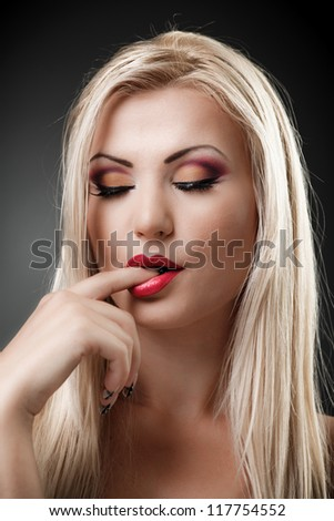 Closeup portrait of a beautiful blond woman sucking her finger - stock photo