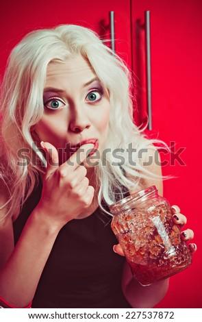 Closeup portrait of a beautiful blonde girl eating jam - stock photo