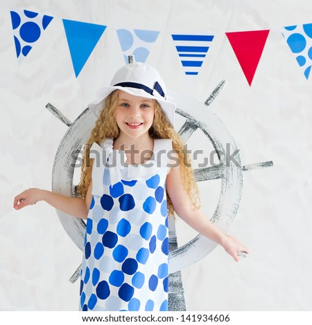 Closeup portrait of a beautiful blonde little girl wearing summer spotted dress and standing in front of decorative wooden steer wheel - stock photo