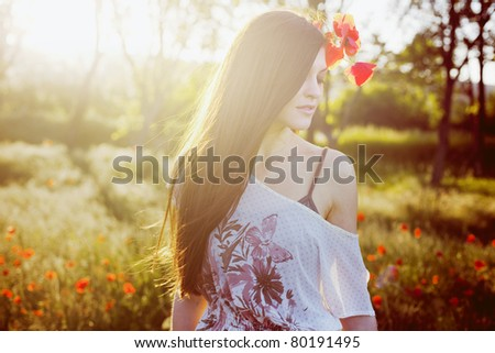 Closeup portrait of a beautiful girl in a poppy field at sunset - stock photo