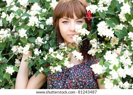 Closeup portrait of a beautiful girl standing among flowers - stock photo