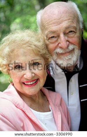 Closeup portrait of a beautiful, happy senior couple.  Focus on her eyes. - stock photo