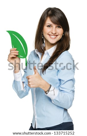 Closeup portrait of a beautiful happy young woman holding eco leaf and showing thumb up sign