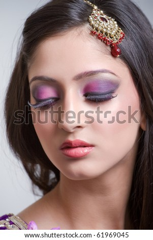 Closeup portrait of a beautiful indian bride with purple makeup
