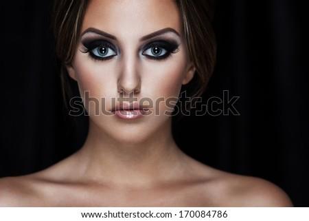Closeup portrait of a beautiful lady on black - stock photo