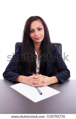Closeup portrait of a beautiful latin businesswoman sitting at desk isolated on white background - stock photo
