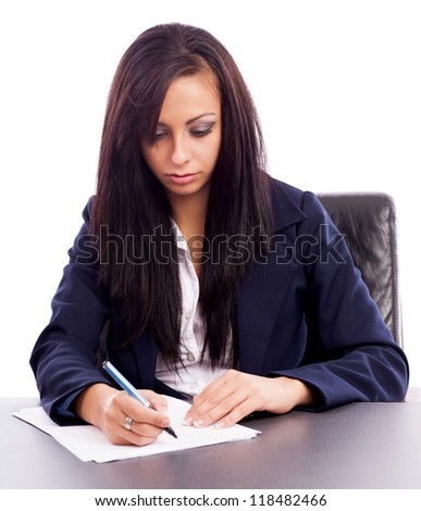 Closeup portrait of a beautiful latin businesswoman writing while sitting at desk isolated on white background - stock photo