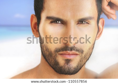 Closeup portrait of a beautiful male model against beach background - stock photo