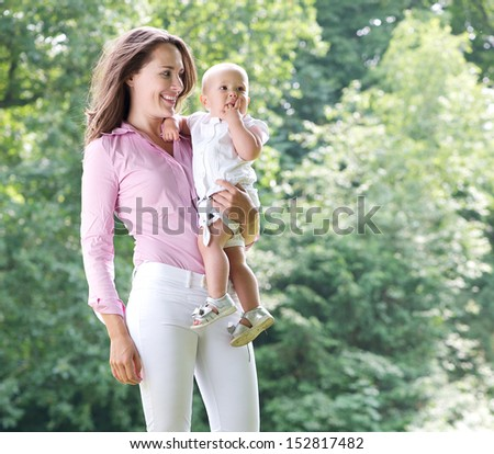 Closeup portrait of a beautiful mother holding baby in the park - stock photo