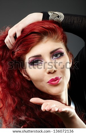 Closeup portrait of a beautiful redhead blowing kiss
