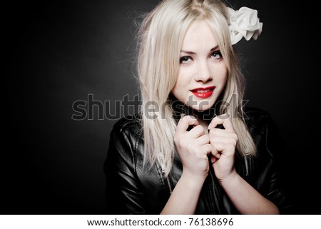 Closeup portrait of a beautiful sexy blond girl in leather jacket and red lipstick - stock photo