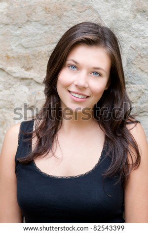 Closeup portrait of a beautiful smiling teen in black top in front of ancient wall - stock photo