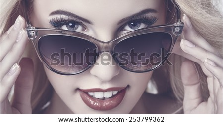 Closeup portrait of a beautiful smiling woman giving a seductive hypnotic look over dark sunglasses. Mate tinted color grading. - stock photo