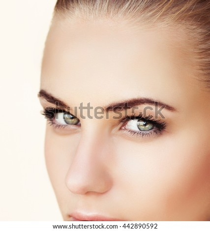 Closeup portrait of a beautiful woman face with green eyes, isolated on beige background, attractive model with natural makeup on perfect skin, beauty salon - stock photo