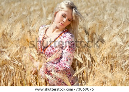 closeup portrait of a beautiful woman in a wheat field - stock photo