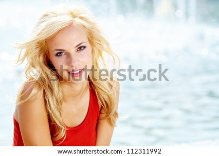 Closeup portrait of a beautiful woman in the city at summer time - stock photo