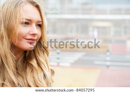 Closeup portrait of a beautiful woman in the city at summer time with modern building at the background - stock photo