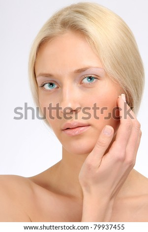 Closeup portrait of a beautiful woman touching her chin, isolated on white