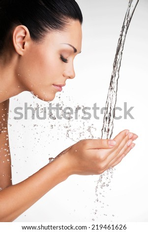 Closeup portrait of a beautiful woman washing her clean face with water   - stock photo