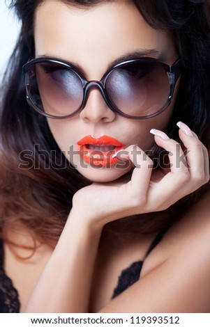 Closeup portrait of a beautiful woman wearing trendy sunglasses