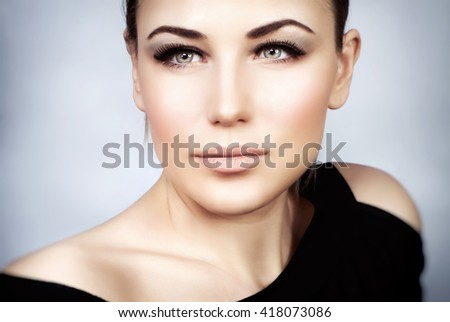 Closeup portrait of a beautiful woman with stylish makeup over gray background, smoky eyes and perfect skin tone, gorgeous seductive model - stock photo