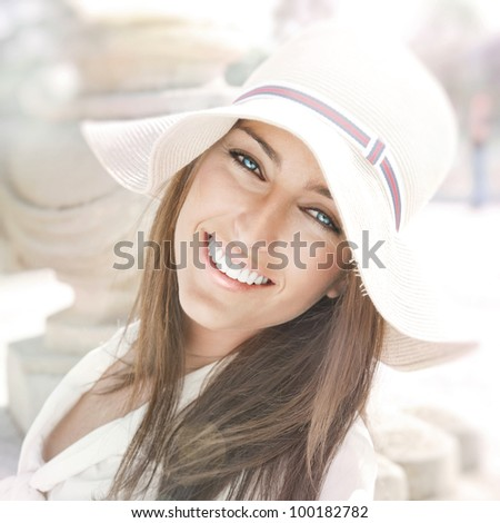 Closeup portrait of a beautiful young woman having a happy thought outdoor in summer park looking at camera