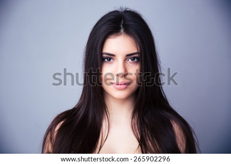 Closeup portrait of a beautiful young woman over gray background. With long hair. Looking at camera.  - stock photo