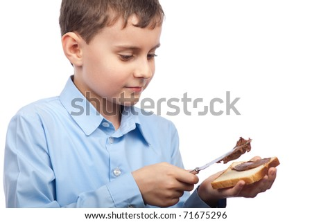 Closeup portrait of a boy spreading chocolate or peanut butter on bread slice