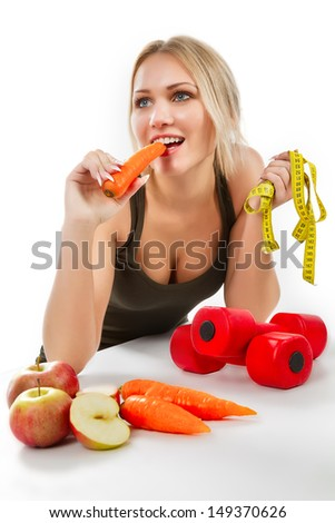 Closeup portrait of a charming woman eating carrot over white background - stock photo