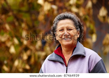 Closeup portrait of a cheerful grandma outdoor in the nature - stock photo