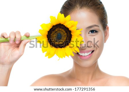 Closeup portrait of a cheerful young woman with a fresh sunflower and a charming smile over white  - stock photo