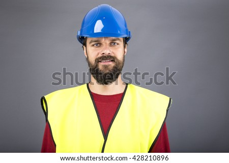 Closeup portrait of a confident engineer with blue hard hat over gray background - stock photo