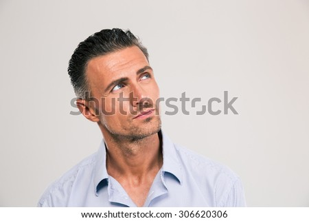 Closeup portrait of a confident man looking away at copyspace over gray background - stock photo