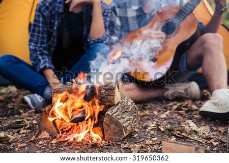 Closeup portrait of a couple sitting with guitar near bonfire in the forest - stock photo