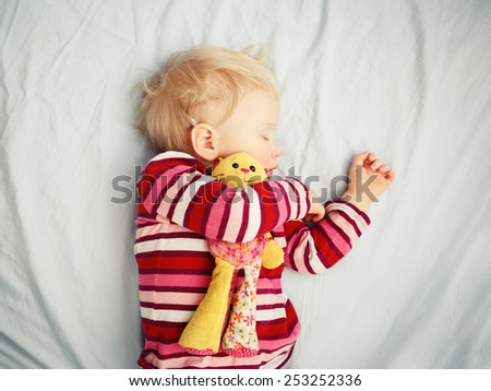 Closeup portrait of a cute adorable white blond Caucasian baby child toddler sleeping dreaming, lying on a bed with comforter toy, indoor - stock photo