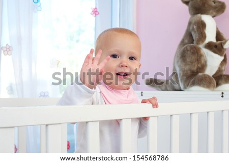 Closeup portrait of a cute baby smiling and waving hello