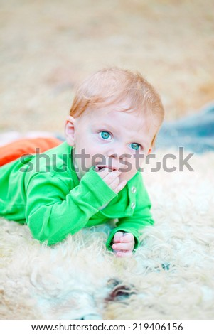 Closeup portrait of a cute blond baby biting his fingers while staring in curiosity - stock photo