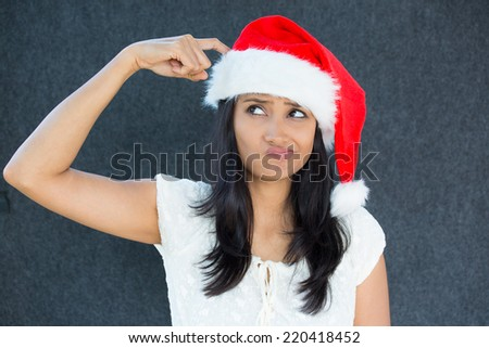 Closeup portrait of a cute Christmas woman with a red Santa Claus hat, white dress, finger on head, confused, thinking what to shop for the holiday season. Emotion on isolated grey background. - stock photo