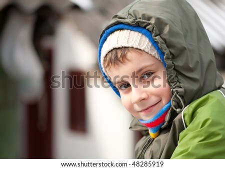 Closeup portrait of a cute kid with winter coat outdoor - stock photo